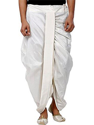 A man wearing a white pre-stitched dhoti which reaches the ankles and a pair of white mojari.