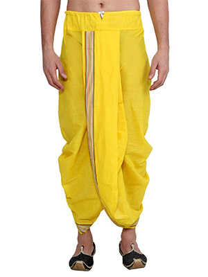 A man wearing a yellow pre-stitched dhoti with a striped border.
