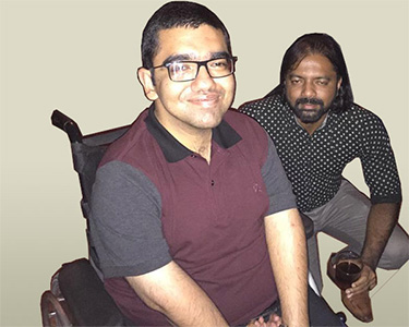 Nipun seated on a wheelchair along with Anish.