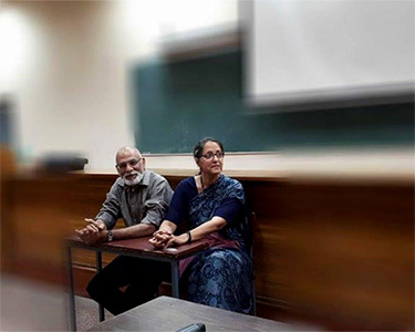 Dr. Navjeevan Singh and Dr. Upreet Dhaliwal seated on a bench in a classroom.