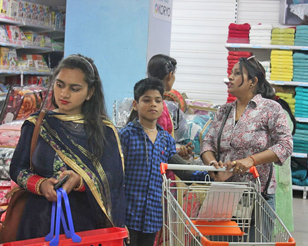 A group of women and a child shopping at one of the aisles in Big Bazaar.