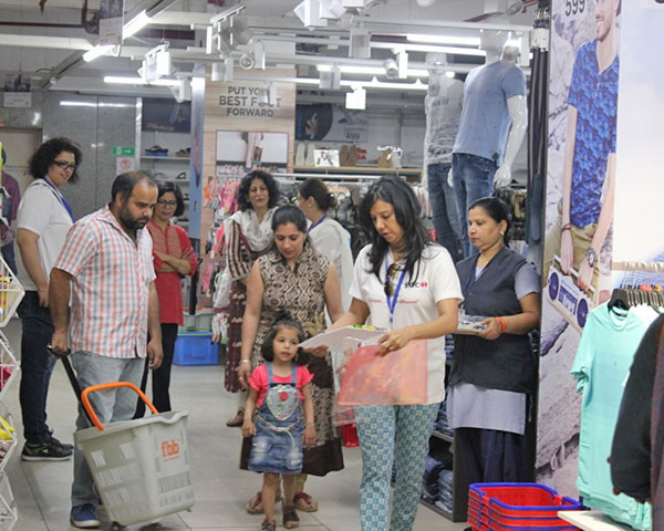 Big Bazaar staff assisting a child and her parent in the clothing section.