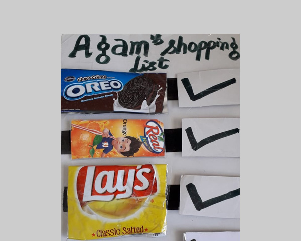 A shopping list with checkmarks against wrappers of biscuits, juice, and chips.