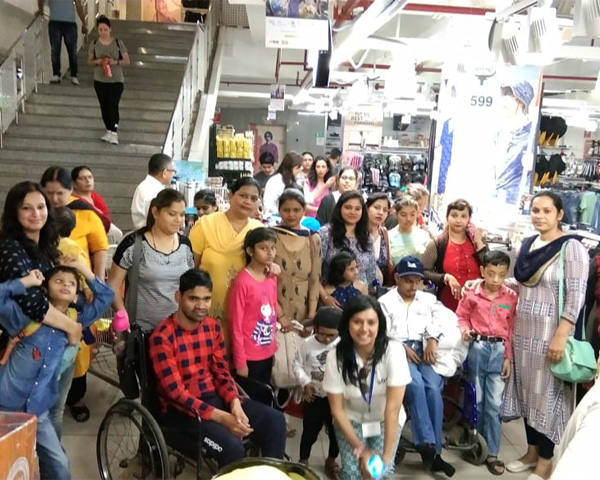 A group of disabled individuals smiling happily and posing for a photograph at a Big Bazaar outlet.