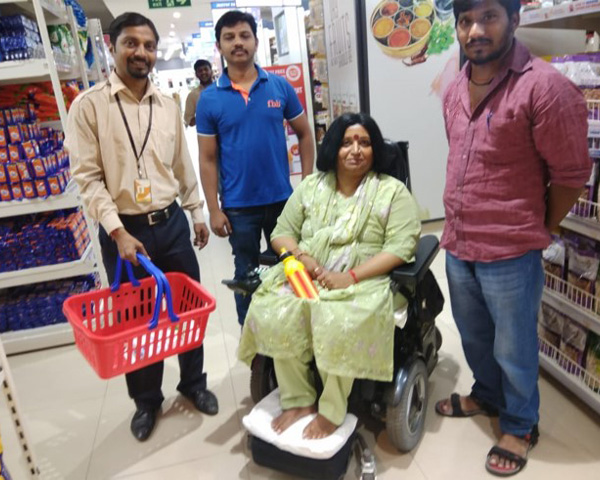 A female wheelchair user posing for a photograph with Big Bazaar staff members.