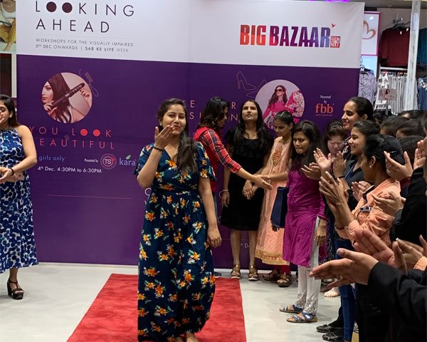 A group of visually impaired women participants cheering for one of the participants as she walks on a red carpet at a training workshop in a Big Bazaar outlet.