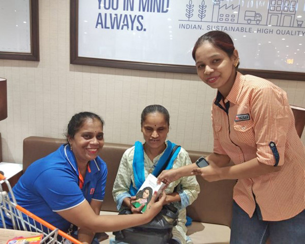 Big Bazaar staff presenting a book to a visually impaired woman.