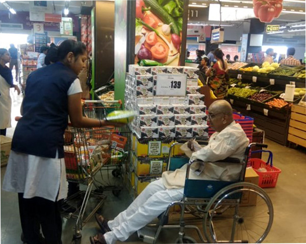 A staff member helping a man in a wheelchair to shop for his groceries.