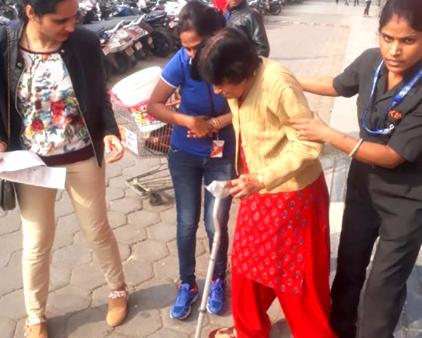 Big Bazaar women staff helping a woman with a disability to exit the premises.
