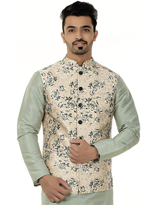 A model wearing a traditional nehru jacket with floral designs on it with a greenish coloured kurta