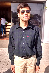 Ajay Minocha dressed in a black shirt with beige trousers.