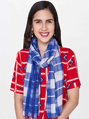 A model wearing a blue and white check pattern scarf along with a red and white coloured top with lines pattern.