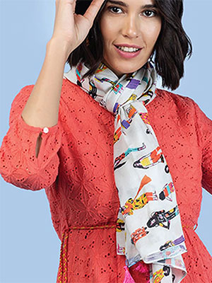 A model wearing a white printed scarf and a light red coloured top having circular cut net pattern.