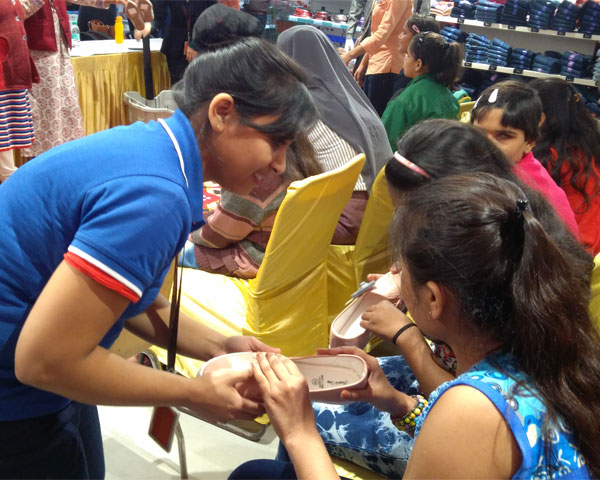 A Big Bazaar woman staff helping two visually impaired girls to feel a pair of shoes.