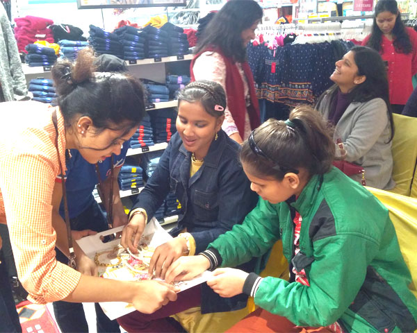 Two visually impaired girls being helped by a Big Bazaar woman staff to recognize and feel jewelry and accessories.