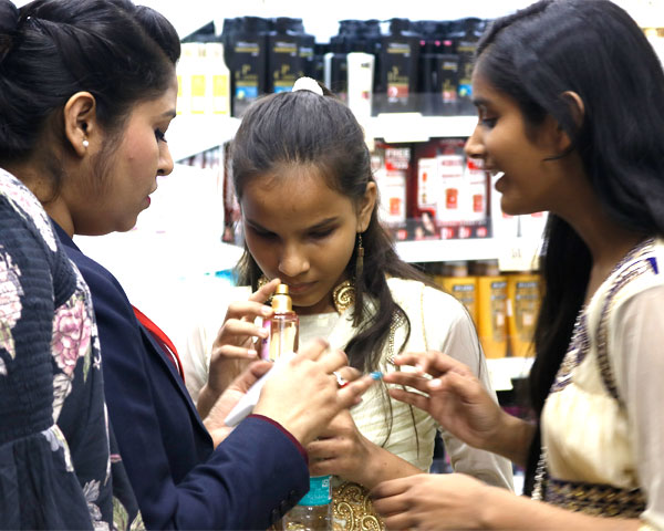 A staff member helping two visually impaired girls to smell and recognize fragrances.