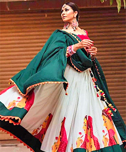 A model wearing a off white coloured lehenga with a off white skirt and rich green coloured dupatta.