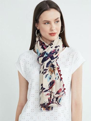 A model wearing a floral printed scarf with pom pom border that displays navy blue coloured pattern design on it along with a white coloured netted top.