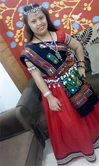 Pooja wearing red coloured lehenga choli and red coloured blouse with a black coloured border on it and a black coloured dupatta having multicoloured designs on it.