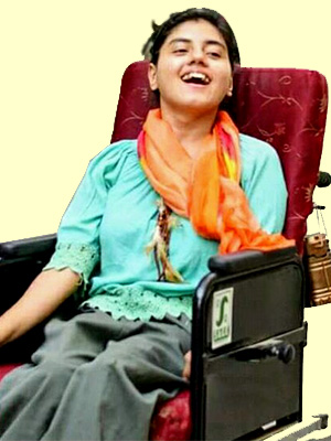 Vinyana seated on wheelchair wearing a light green coloured top and olive coloured pants along with orange and red coloured scarf.