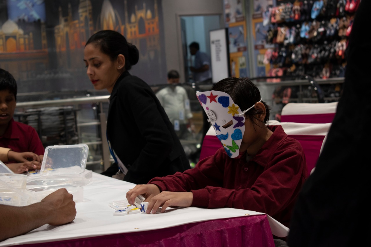 Child wearing a colorful mask and making an artwork