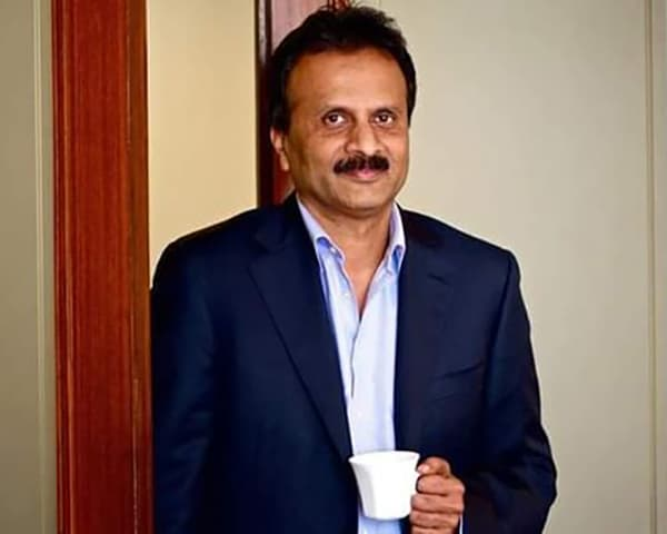 Image of V G Siddhartha holding a white coffe mug