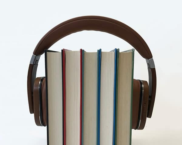 four books stacked with headphone over them