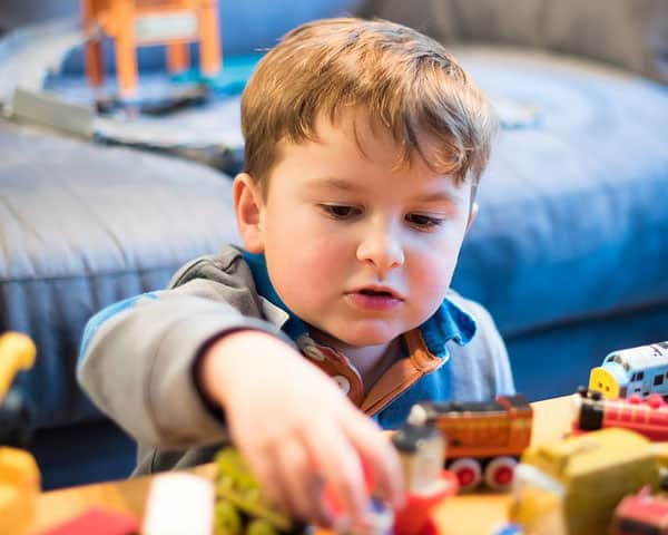 a child playing with small toy trains