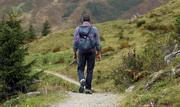 a man with backpack walking on a mountain trail