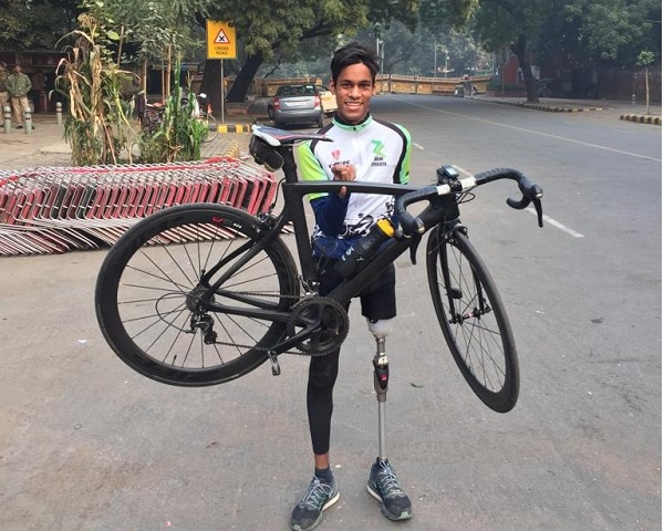 himanshu holding up his cycle with one finger
