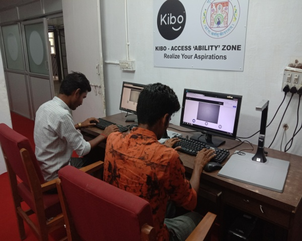 Two visually impaired men looking at a computer using Kibo XS