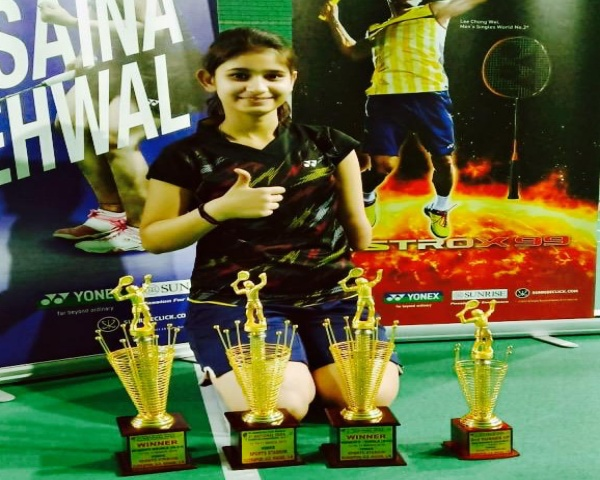 Palak Kohli standing in front of her trophies