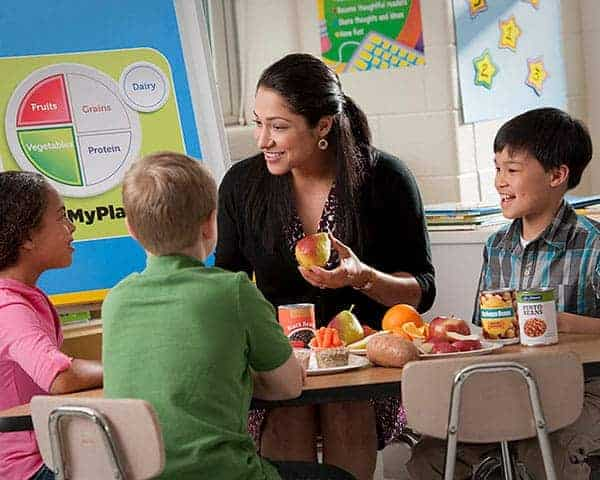 Teacher with an apple and a group of children sitting around a table of cans and fruits