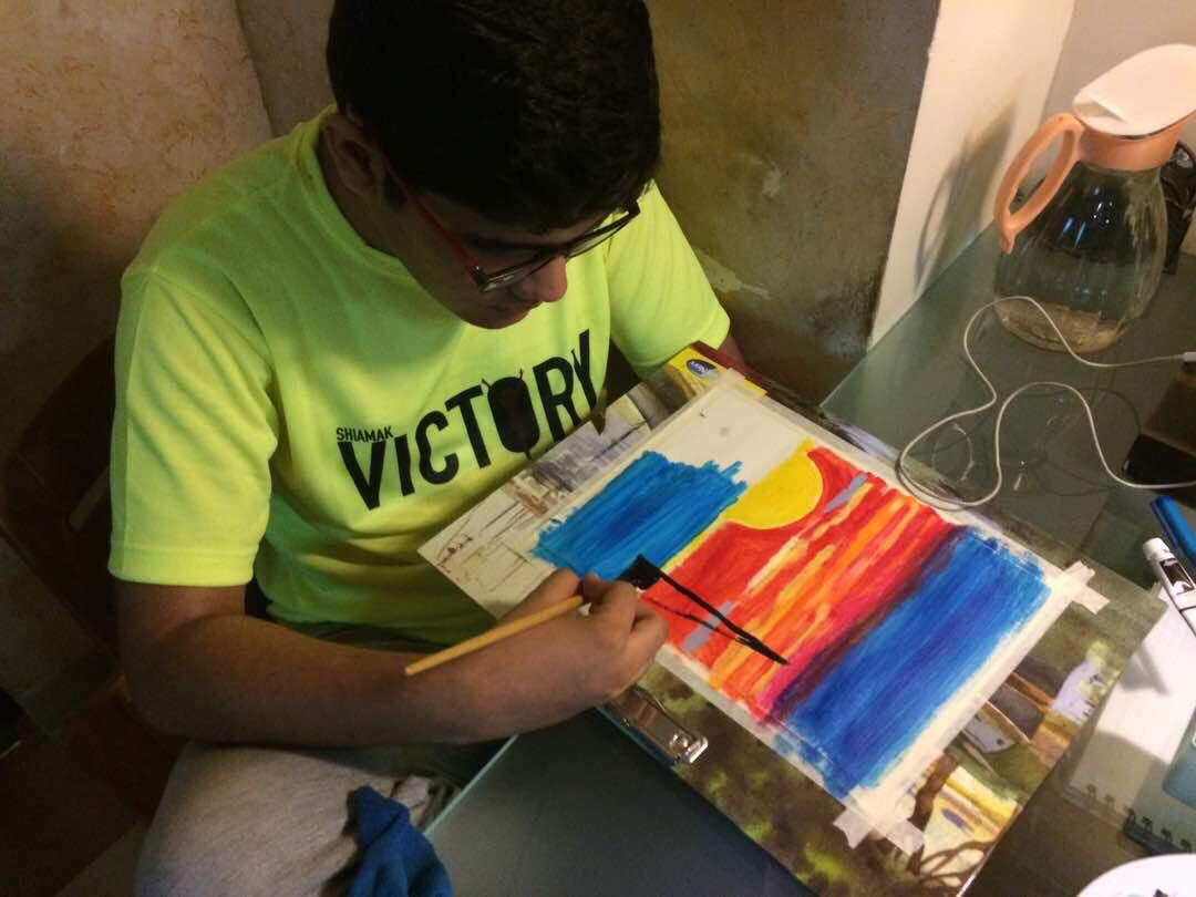 A boy painting a drawing of scenery.