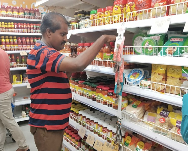 Man stocking items at a shelf in a shop