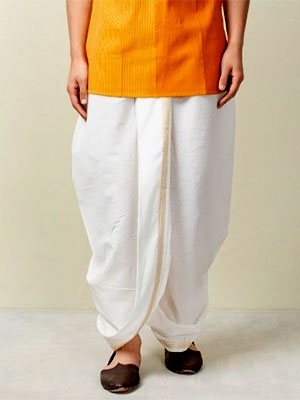 A man wearing a white dhoti with golden border and a yellow orange kurta.
