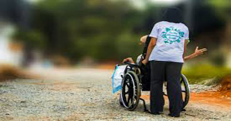 Person in a wheelchair with caregiver