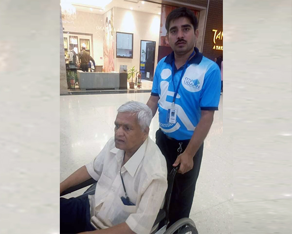 Man in wheelchair being assisted by a myUDAAN caretaker