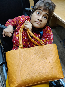 Jasmina holding a light brown coloured leather bag.