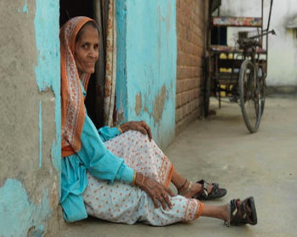 A woman sitting at the doorstep of her home