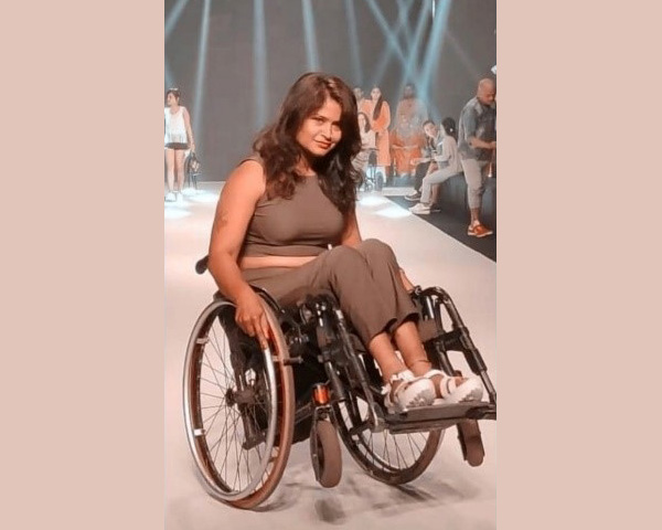 Nisha flaunting a two-piece sleeveless crop top and pants on a runway