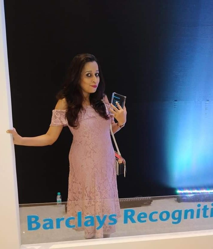 Shagun holding Barclays Award in hand and posing in style.