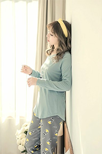 A model wearing a pale green top and light grey pyjama.