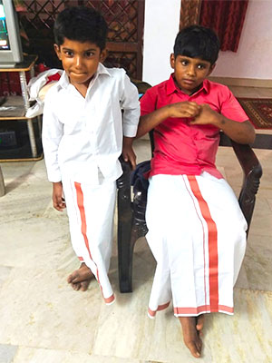 Shiva and his brother wearing identical white dhotis with red borders and shirts.