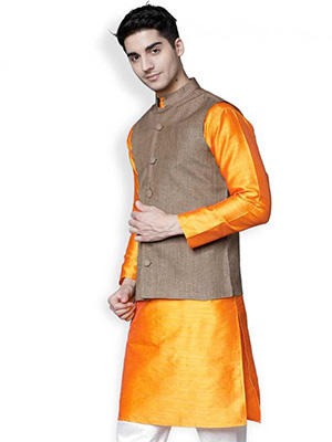 A model wearing a brown coloured jacket over a orange coloured kurta.