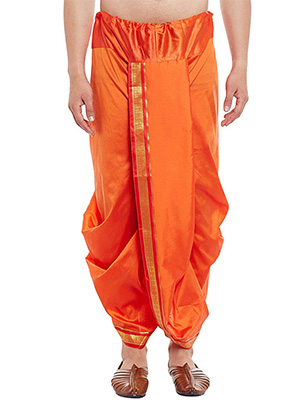 A man wearing an orange pre-stitched dhoti with a red and golden border and brown leather mojari.