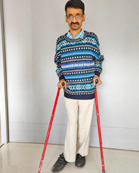 Mayur is wearing a patterned shirt and trousers and is holding a pair of red coloured crutches.