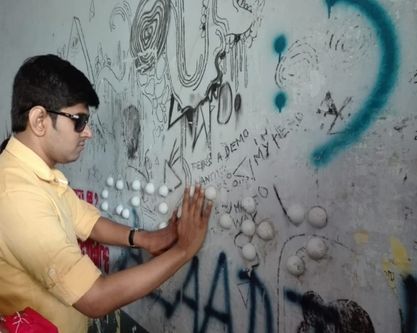 Visually impaired person experiencing the braille graffiti
