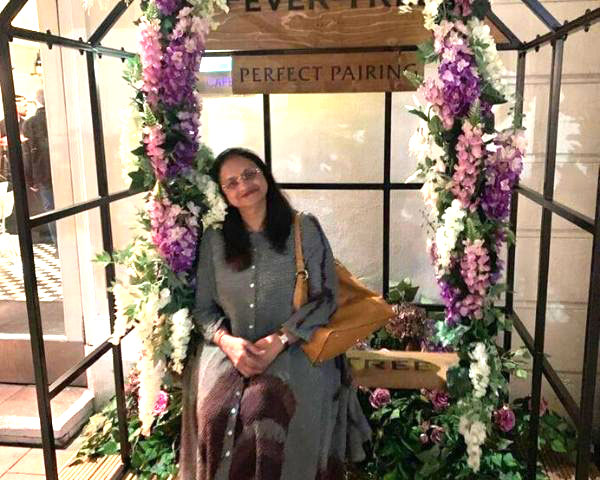 Dr Rekha seated on a swing like place decorated with flowers