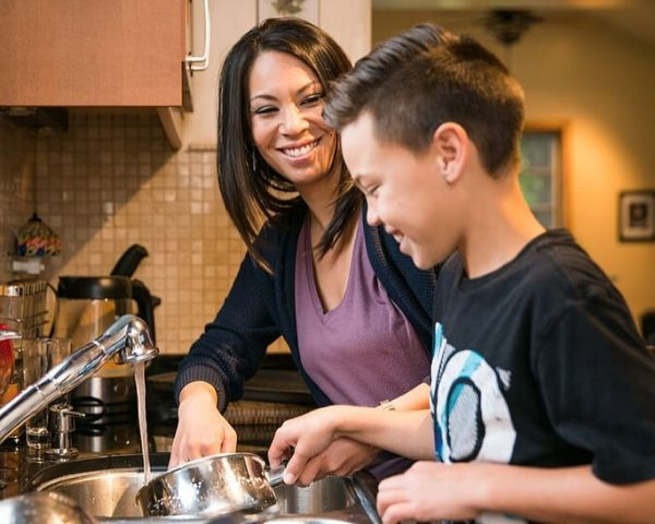 A mother and his son smiling in kitchen